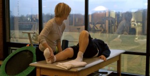 Amy Lynch, MPT, Physical Therapist  stretches a patient at TheraSport Physical Therapy